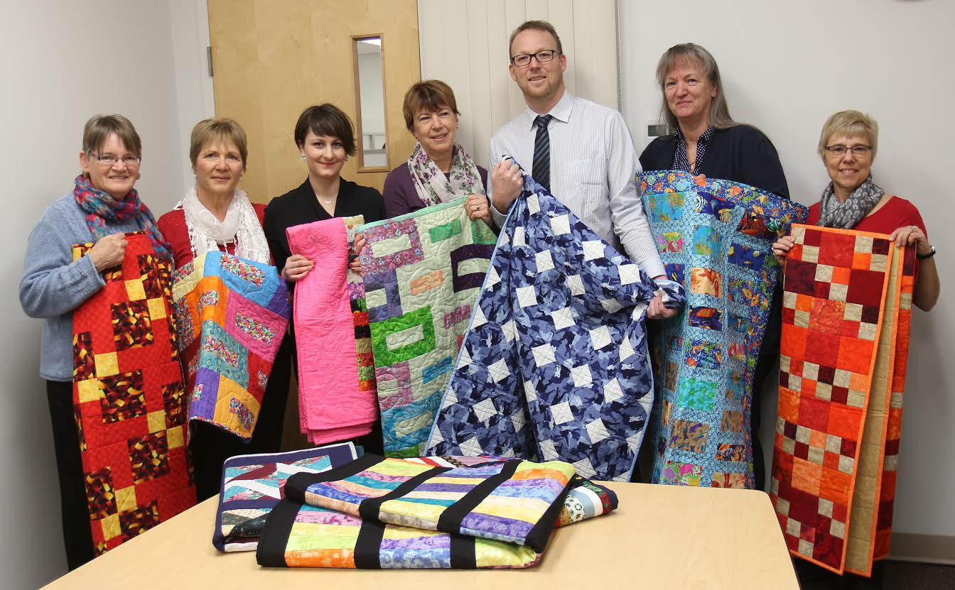 Guild Members pose with U of L Counselling Services with donated Community Quilts to help students in need.